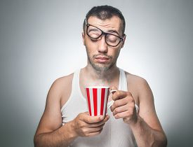 picture of nerds  - Sleepy funny man holding cup coffee or tea beginning a new day - JPG