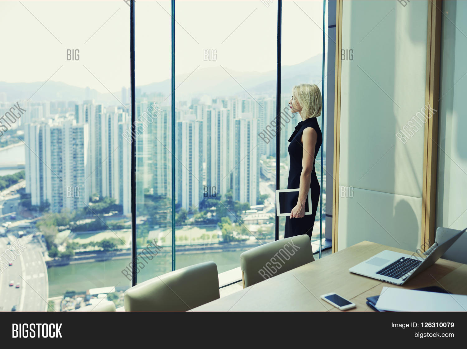 Blonde Woman Proud CEO Is Holding Touch Pad And Looking In Office Window  With Cityscape While