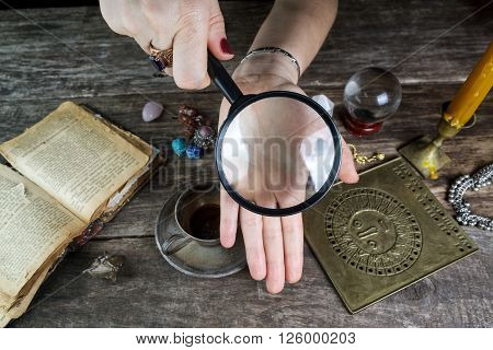 Palmistry. Fortune teller woomens hands ob wooden table