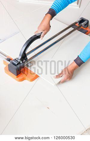 Industrial tiler builder worker working with floor tile cutting equipment