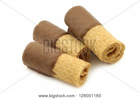 rolled up crispy chocolate wafers on a white background