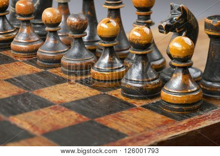 vintage wooden black chess pieces on chessboard with focus on pawns