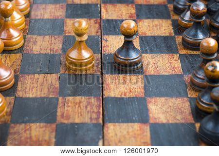vintage wooden black and white pawn pieces in opposition at game start on chessboard