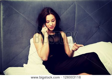 Woman talking on the phone in bedroom.