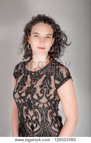 Portrait Of A Young Woman With Black Hair And Black Blue Dress..