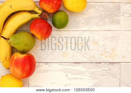 Banana, Pear, Lime, Apples And Lemons In The Corner On The Wooden Background