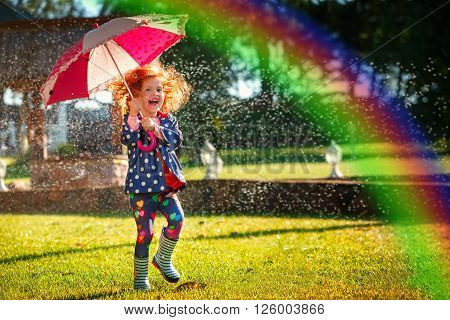 Laughing girl in the rain under umbrela with a rainbow.