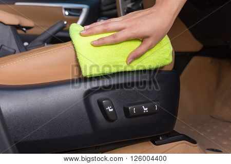 A woman hand with yellow microfiber cloth cleaning in car sittings electricity.