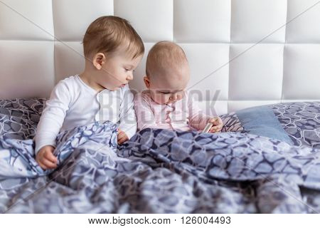 Baby boy and girl twins on parents bed in the early morning