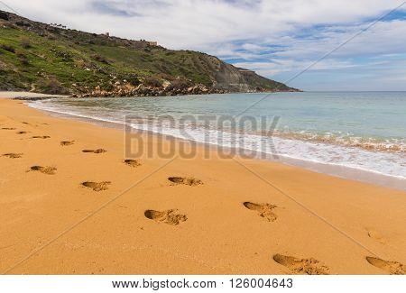 Footprints in sand at Ramla Bay in Gozo island Malta