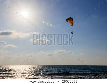parachute jumper on motorized parachute flying over the sea