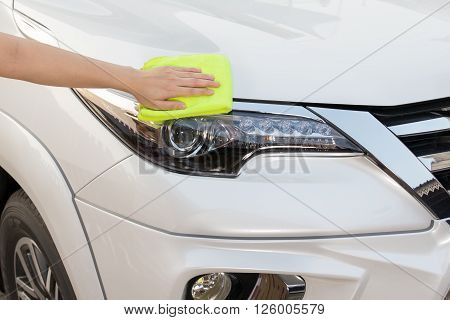 A woman hand with yellow microfiber cloth cleaning big white car.