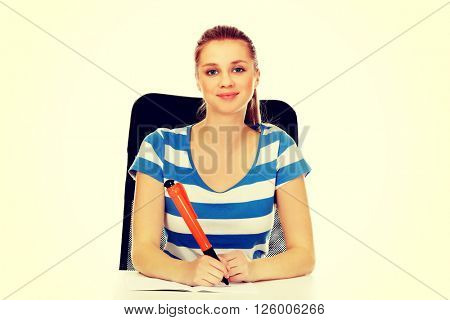 Teenage woman doing notes with a huge pen