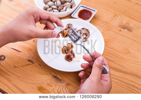 Closeup on cockles being extracted from its shell for consumption with chili dips. Delicacy among Asians.