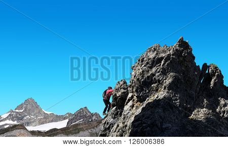Hiker climbs on rock in the background mount Zinalrothorn - Pennine Alps, Switzerland