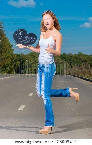 Happy Slim Girl Hitchhiking On The Asphalt Road