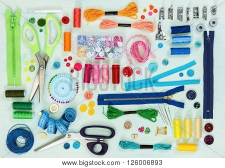 Sewing tool and accessories on painted background blue color top view. Flat lay.