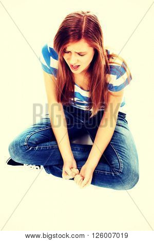 Angry teenage woman sitting on the floor and screaming