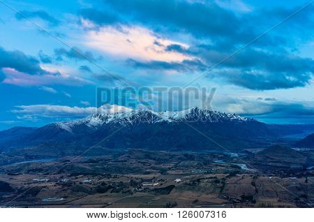 Mountain valley aerial view at dusk. Coronet peak view of Arrowtown village and valley. Otago New Zealand. Winter landscape at sunset