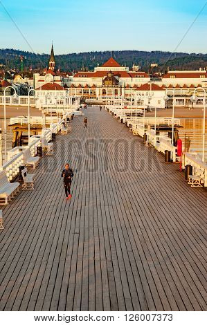 SOPOT, POLAND - APRIL 10, 2015: People walking on the Sopot Pier built in 1827. At 511m, the pier is the longest wooden pier in Europe.