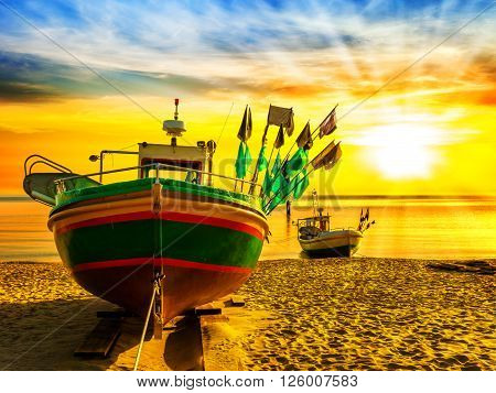 Picturesque landscape of a sunrise with a boat on beach in Sopot Poland.