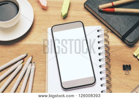 Closeup of blank white smartphone screen on wooden table with office tools and coffee. Mock up