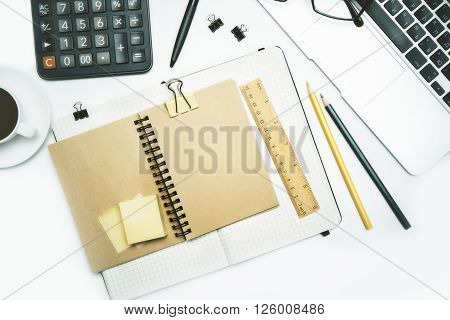 Topview of desktop with copybook and various office tools