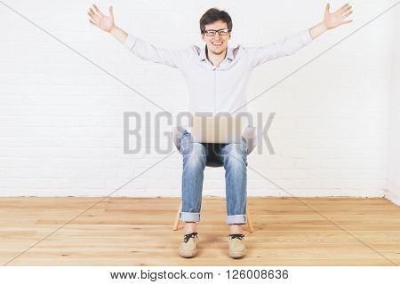 Excited caucasian male with hands up high sitting in brick interior with notebook on his lap