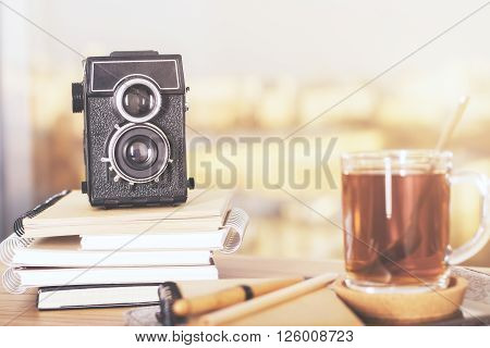 Wooden desktop with retro camera on copybook stack and cup of tea