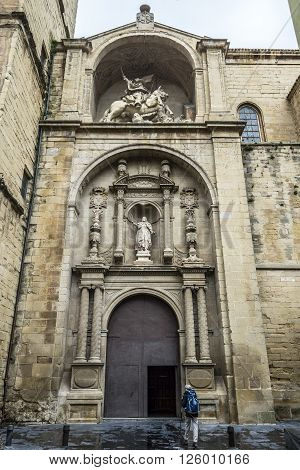 Logroño Spain - April 9 2016. Pilgrim on Way of Saint James in front of principal facade of Santiago el Real church in Logroño. This church is dedicated to St. James the patron saint of Spain. La Rioja.
