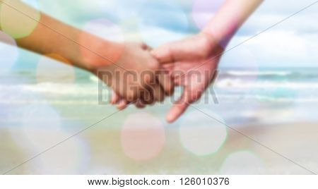 sweet dreamy and de-focused photo ; two person holding by hands against the sea