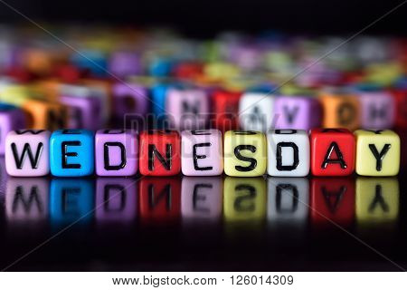Wednesday word with reflection on colorful dice