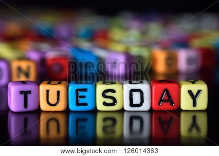 Tuesday word with reflection on colorful dice