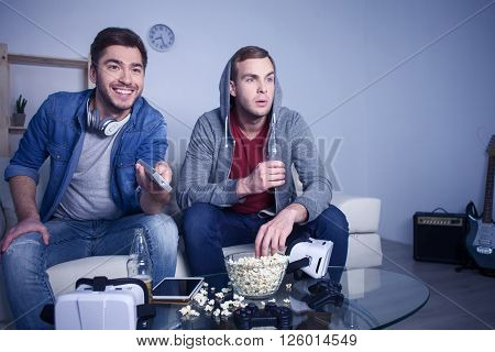 Cheerful young friends are watching tv with enjoyment. They are sitting on couch. The man is holding a remoter and smiling. His friend is eating popcorn and drinking beer