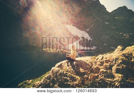Woman meditating yoga sitting on cliff alone sun light Travel healthy Lifestyle concept lake and rocky mountains landscape on background outdoor