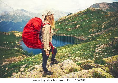 Young Woman with red backpack mountaineering Travel Lifestyle concept lake and mountains landscape on background vacations adventure journey outdoor