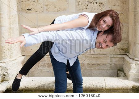 Happy Man In Love Holding Brunette Woman Piggy Back In Vacation