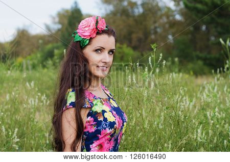 beautiful woman with long hair decorated with artificial flowers stands in a field among the tall grass on a summer evening