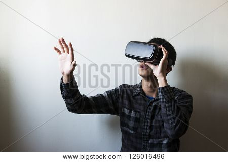 man using the virtual reality headset on White wall