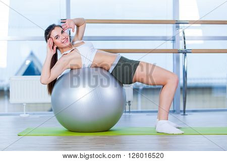 Beautiful young girl doing exercises with fit ball at gym