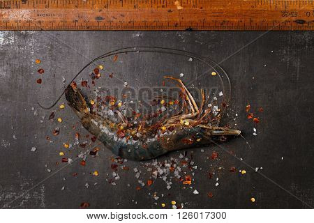 raw shrims with spice on black stone board