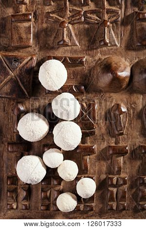 kurt kurut - asian dried yogurt balls on carved wooden background