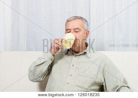 Senior man enjoys drinking coffee or tea at home.