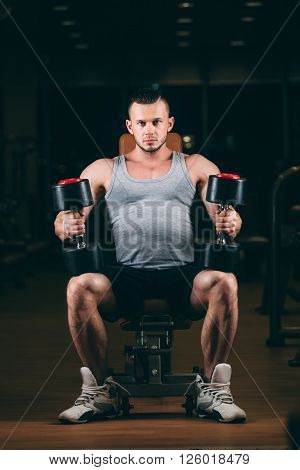 sport, bodybuilding, weightlifting, lifestyle and people concept - young man with dumbbells flexing muscles in gym.