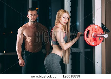 Young couple exercising in gym with weights the man seems to be the personal trainer. ** Note: Shallow depth of field