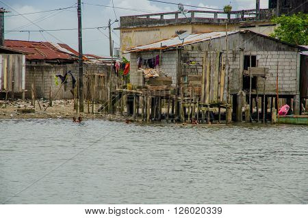 Muisne, Ecuador - March 16, 2016: Slums in poor section of the city, in the coast of Ecuador, with houses on poles over the sea water