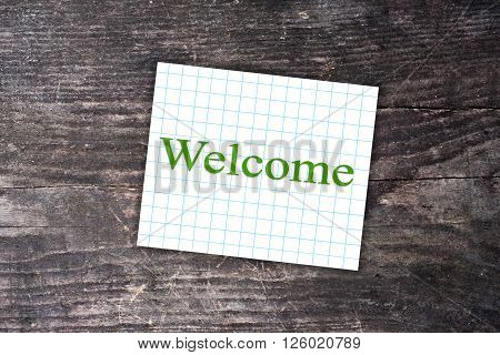 Welcome text on a checkered note. Dark wooden background