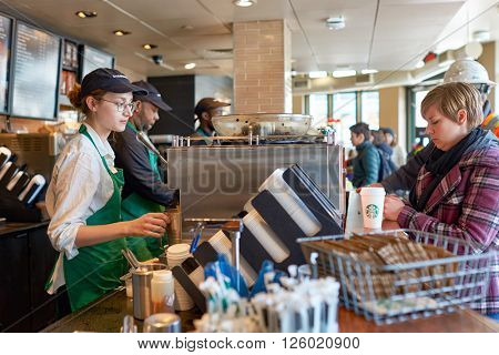 NEW YORK - CIRCA MARCH 2016: worker at Starbucks Cafe. Starbucks Corporation is an American global coffee company and coffeehouse chain based in Seattle, Washington
