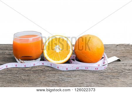 Closeup of orange juice and oranges on a wooden floor.