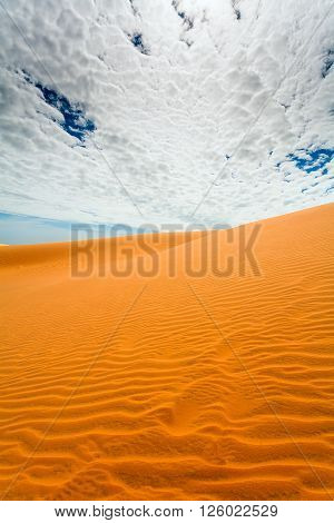 sand dune patterns and clouds over land